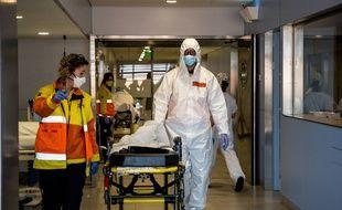 En Catalogne, des soignants tranfèrent un patient atteint du Covid-19.
