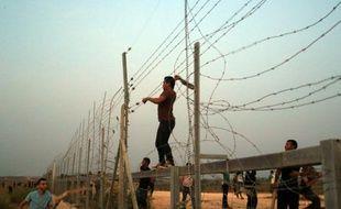 Des Palestiniens s'attaquent aux barbelés à la frontière entre Gaza et Israël, lors d'affrontements avec les forces de l'ordre israéliennes le 12 octobre 2015