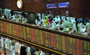 Des boursiers suivent l'évolution des indices à la Bourse du Koweit, le 16 septembre 2013