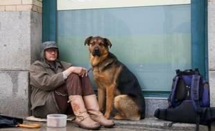 Un sans-abri avec son chien dans la rue.