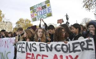"""High school students hold on November 13, 2014 a banner during a demonstration in the center of Paris, reading: """"Angry High School Students"""" and a placard, saying """"Remi, we're not forgeting you"""" in reference to ecological militant Remi Fraisse killed on October 26 by a police grenade during clashes at a demonstration in southern France. AFP PHOTO / THOMAS SAMSON"""