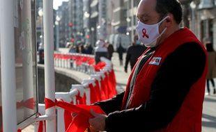 Un homme accroche des rubans rouges, symboles de la lutte contre le Sida, le 1er décembre, à Gijon, en Espagne.