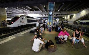 Des voyageurs bloqués attendent sur les quais de la gare Montparnasse, vendredi 27 juillet.