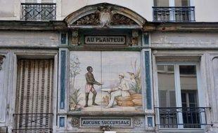 Un Noir en short rayé sert un café à un Blanc en costume: cette céramique en plein coeur de Paris est l'une des rares traces architecturales laissées par la colonisation dans la capitale, qui a pourtant largement profité de la traite négrière.