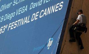 Haute voltige pour les ouvriers en charge de fixer  l'affiche officielle de la 63ème édition au Palais des Festivals.