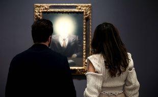 Des visiteurs regardent «Le principe du plaisir» de René Magritte, avant l'ouverture de la vente, le 10 novembre 2018 à New York.