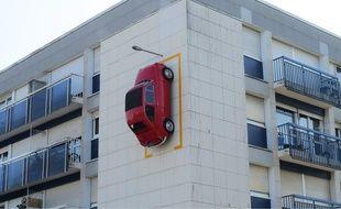 Une Fiat 500 rouge est garée à la verticale sur la façade d'un immeuble du quartier Bellevue à Nantes.
