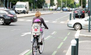 Illustration d'une cycliste transportant son enfant à vélo, ici dans les rues de Rennes.