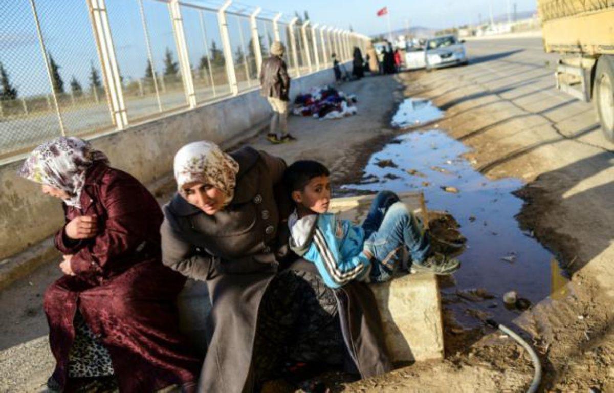 Des Syriens attendent au point de passage d'Oncupinar, près de la ville de Kilis en Turquie, de pouvoir retourner en Syrie, le 9 février 2016 – BULENT KILIC AFP