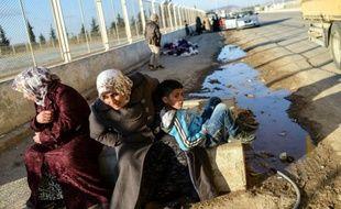 Des Syriens attendent au point de passage d'Oncupinar, près de la ville de Kilis en Turquie, de pouvoir retourner en Syrie, le 9 février 2016