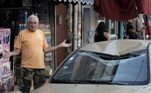 Un habitant de Tel Aviv devant un véhicule touché le 10 juillet 2014 par une roquette palestinienne