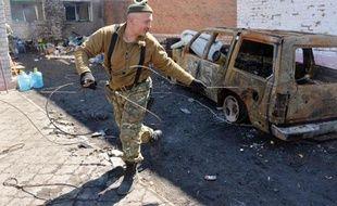 Un homme s'apprête à évacuer une voiture calcinée, le 15 avril 2015 dans la banlieue de Marioupol