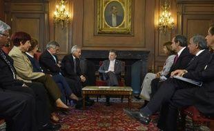Le président colombien, Juan Manuel Santos (c) lors d'une réunion à Bogota, le 28 octobre 2015, de la commission chilienne de soutien au processus de paix qui doit se dérouler à la Havane, à Cuba, entre le gouvernement colombien et les Farc