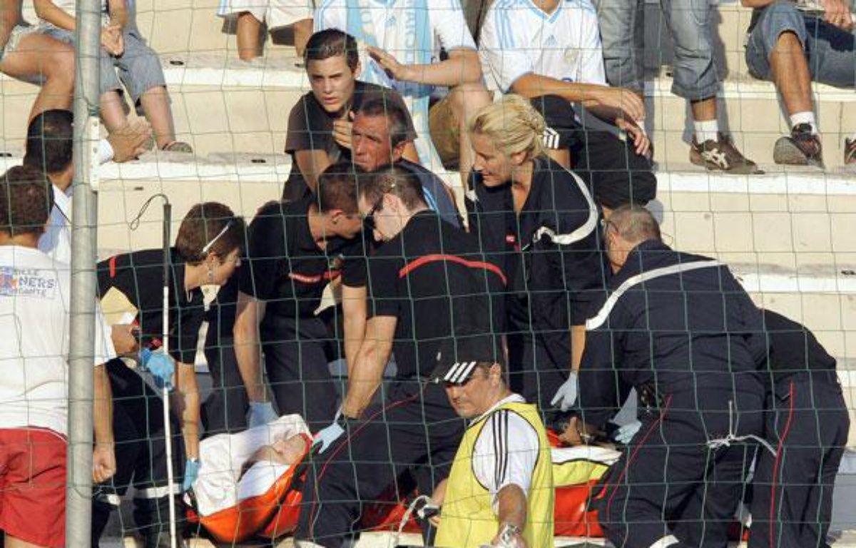 Un supporter marseillais pris en charge par les pompiers après une chute lors du match entre Marseille et Lille, le 16 août 2009. – M.Gangne / AFP