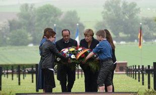 François Hollande, Angela Merkel et quatre jeunes déposent une gerbe  le 29 mai 2016 au cimetière allemand de Consenvoye