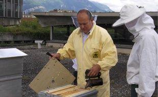 Claude Merle enfume les abeilles d'une des ruches installées sur le toit de la mairie.