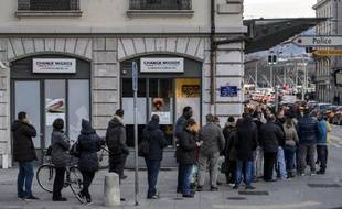 People queue to change their Swiss francs at a currency exchange office on January 15, 2015 in Geneva. In a shock announcement on January 15, Switzerland's central bank said it was ending a three-year bid to artificially hold down the value of the Swiss franc against the euro, in a move that immediately sent the safe haven currency soaring. Following the announcement, the Swiss franc strengthened 29 percent to 0.8517 against the euro. AFP PHOTO / FABRICE COFFRINI