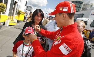 Le sextuple chamion du monde de formule 1 Michael Schumacher signe la casquette d'un enfant, au grand prix de Nürburgring, le 22 juillet 2007
