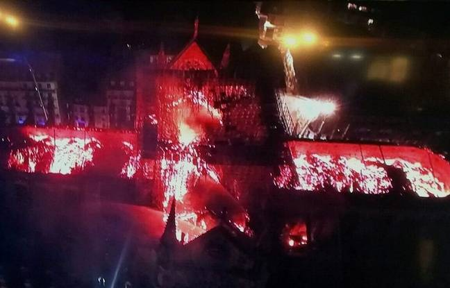 An image taken from a television screen shows an aerial view of the Notre-Dame Cathedral engulfed in flames on April 15, 2019, in the French capital Paris. - A huge fire swept through the roof of the famed Notre-Dame Cathedral in central Paris on April 15, 2019, sending flames and huge clouds of grey smoke billowing into the sky. The flames and smoke plumed from the spire and roof of the gothic cathedral, visited by millions of people a year. A spokesman for the cathedral told AFP that the wooden structure supporting the roof was being gutted by the blaze. (Photo by - / AFP)