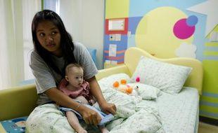 La thaïlandaise Pattaramon Chanbua, mère porteuse thaïlandaise, et son bébé trisomique Gammy, à Samitivej en Thaïlande le 4 août 2014
