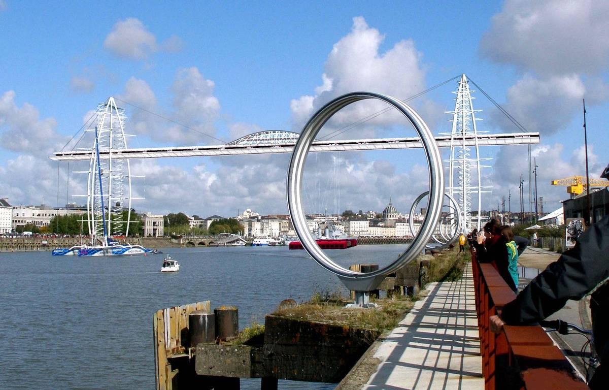 Le pont, tel qu'il pourrait être vu de puis le Hangar à bananes. Au-dessus du fleuve, en rouge, la nacelle en mouvement. – Image de synthèse NPPI