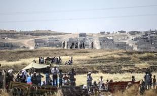 Des soldats turcs (au 1er plan) montent la garde alors que des Kurdes syriens se massent derrière des barbelés du côté syrien de la frontière turco-syrienne, près de Kobané, le 26 juin 2015.