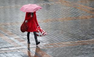 Lille, le 29 janvier 2013. Une jeune fille marche sous la pluie.