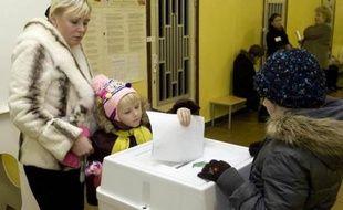 Un enfant glisse un bulletin dans l'urne sous l'oeil de sa mère à Moscou, le 2 décembre 2007.