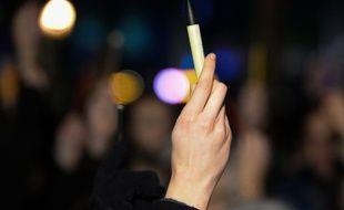 Une manifestante brandi un stylo pour exprimer son soutien aux victimes de l'attenta contre Charlie Hebdo le 7 janvier 2015 à Bruxelles