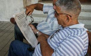 Des hommes lisent un journal indiquant la baisse de prix de certains aliments, à La Havane le 22 avril 2016