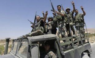 Des soldats libanais font le V de la victoire à la sortie d'Aarsal, près de la frontière syrienne, le 4 août 2014