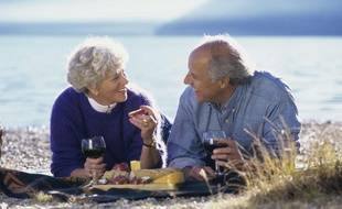 Un couple de seniors pique-nique sur la plage.