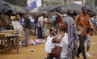 Une femme tient son enfant à Abidjan en Côte d'Ivoire, le 26 octobre 2015.
