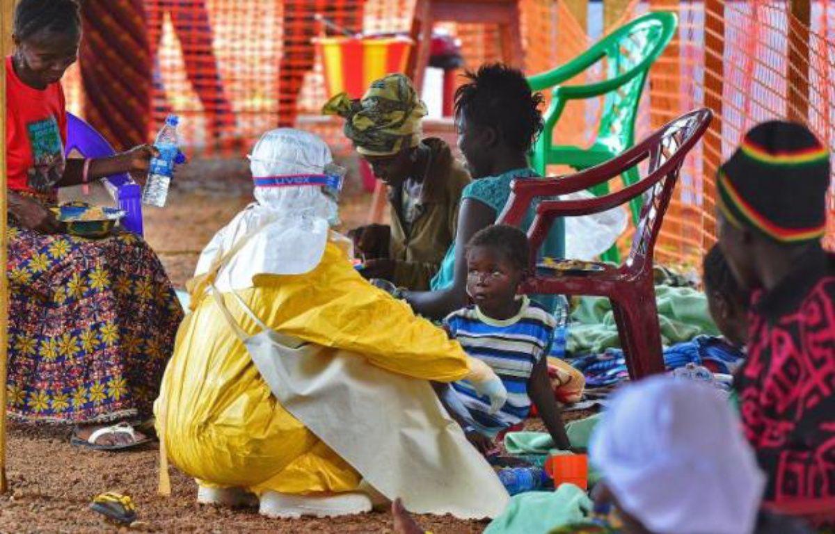 Un employé de MSF donne à manger à un enfant victime d'Ebola, le 15 août 2014 dans le centre de Kailahun, en Sierra Leone – Carl de Souza AFP