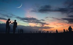 Illustration d'un groupe de personnes en plein air au couchant, avec la lune dans le ciel