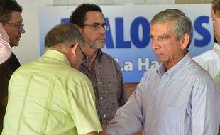 Robrigo Grande (g) des Farc salue le représentantdu gouvernement Jorge Enrique Mora à La Havane le 3 décembre 2014