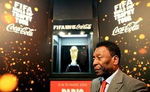 Brazilian football legend Pele answers journalist's questions next to the FIFA World Cup trophy during a press conference, on March 9, 2014 outside the Hotel de Ville in Paris. The FIFA World Cup trophy arrived with its ambassador Pele in Paris on March 9, 2014 and will be exhibited on the Hotel de Ville plaza until March 10. AFP PHOTO / FRANCK FIFE