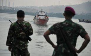 Des forces de l'ordre indonesiennes regardent un bateau d'immigrants s'approcher des côtes le 31 août 2012
