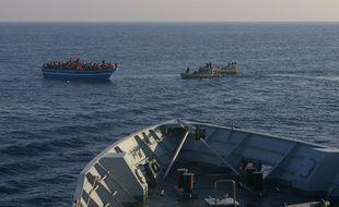 Des navires de la marine italienne approchent un bateau de migrants, en avril 2014.