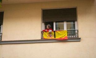 Une femme à son balcon à Madrid protestant contre le maintien du confinement, le 15 mai 2020.