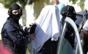 Yassin Salhi entre des policiers lors de la perquisition à son domicile le 28 juin 2015 à Saint-Priest