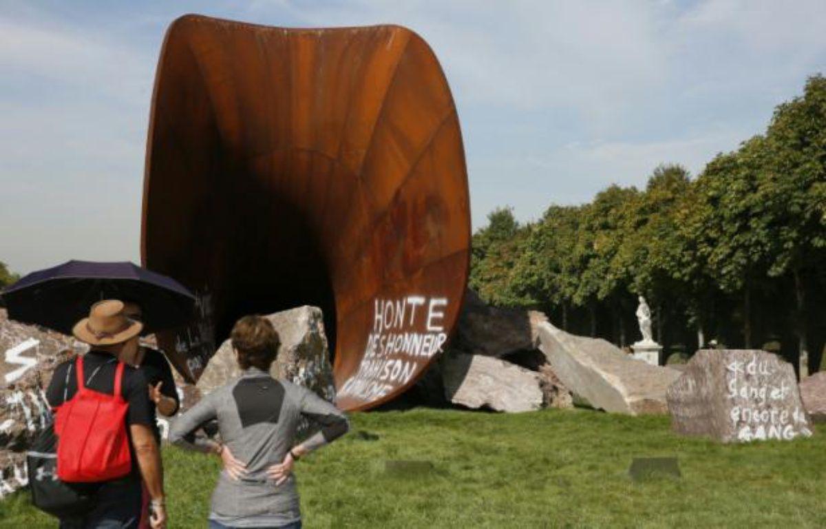 Des visiteurs s'arrêtent devant une des  œuvres de Anish Kapoor vandalisée par des tags antisémites, dans les jardins du Château de Versailles le 11 septembre 2015 – PATRICK KOVARIK AFP