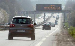 Des voitures passent sous un panneau d'avertissement du pic de pollution.