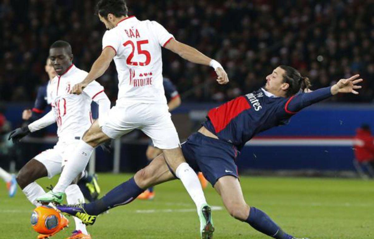 Le Lillois Marko Basa (de dos en blanc) taclé par le Parisien Zlatan Ibrahimovic, lors d'un match de L1 au Parc des Princes, le 22 décembre 2013. – Sipa