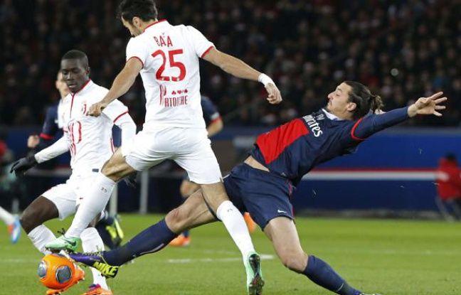 Le Lillois Marko Basa (de dos en blanc) taclé par le Parisien Zlatan Ibrahimovic, lors d'un match de L1 au Parc des Princes, le 22 décembre 2013.