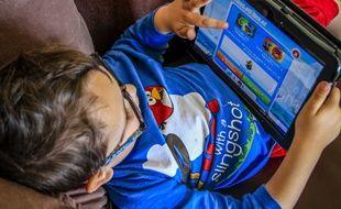 Un garçon jouant à un jeu vidéo sur une tablette.