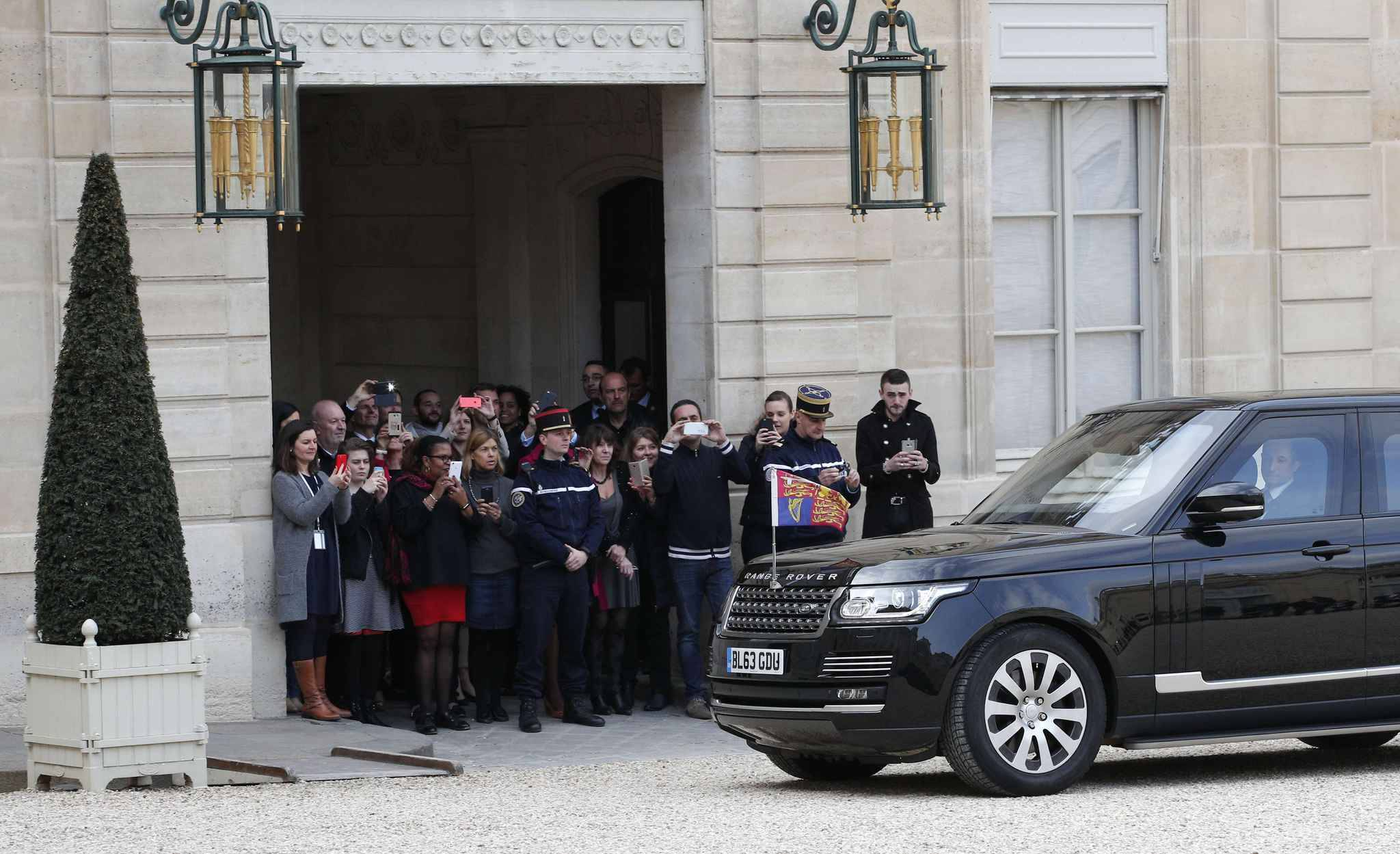 Elysee Palace employees watch Prince William and Kate, Duchess of Cambridge arriving in a car, in Paris, Friday March 17, 2017. Prince William and his wife Kate are coming to Paris to meet the French president as Britain gets ready to launch divorce proceedings from the European Union.