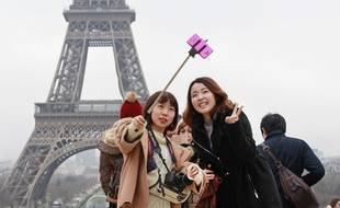 Des touristes avec une perche à selfie, à Paris le 6 janvier 2015