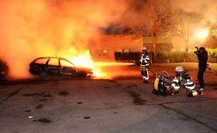 Des pompiers tentent d'éteindre des voitures incendiées à Kusta, une banlieue de Stockholm lors des émeutes en Suède le 21mai 2013.