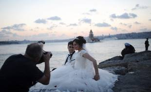 Un couple de jeunes mariés pose devant la Tour de Léandre, près d'Istanbul, le 20 août 2013.